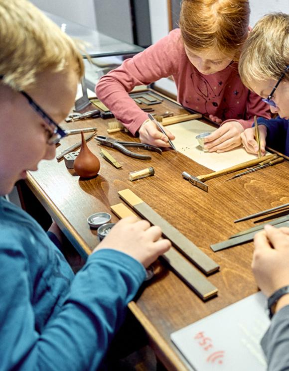 Kinder probieren sich am Uhrmachertisch