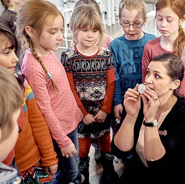Kindergruppe bestaunt eine Taschenuhr