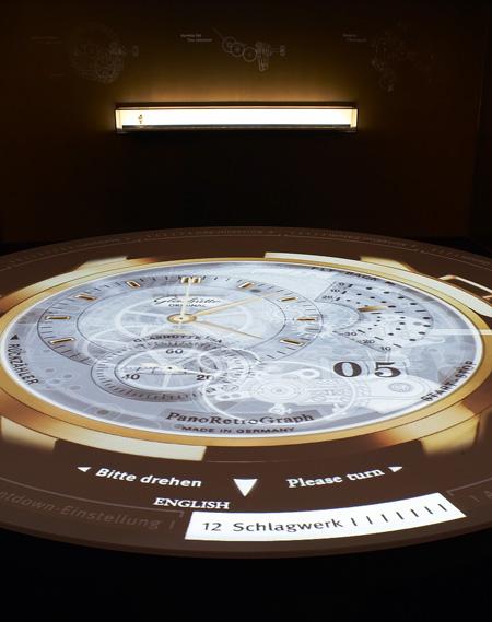 Besucher informieren sich am Projektionstisch über eine mechanische Uhr