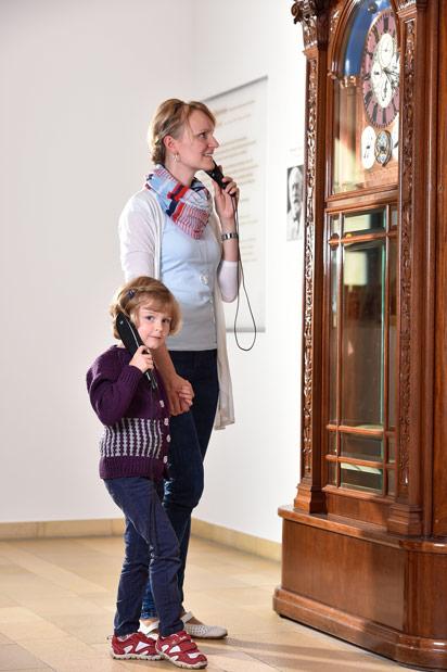Mutter und Kind mit Audioguides vor der Goertz-Uhr